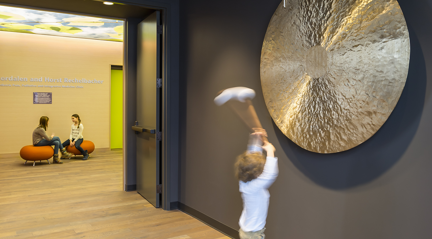 Entrance to children's pain clinic in hospital with large gong on wall